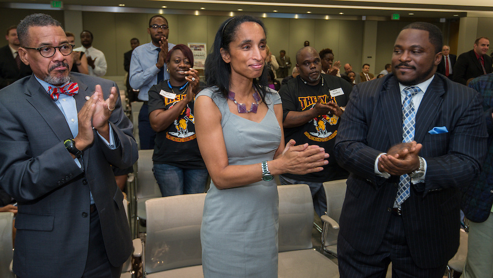 William Paul Thomas, left, Alison Leland, center, and Dameion Crook, right, applaud the naming of Young Men's College Preparatory Academy for Congressman Mickey Leland during a meeting of the Houston ISD Board of Trustees meeting, September 11, 2014.