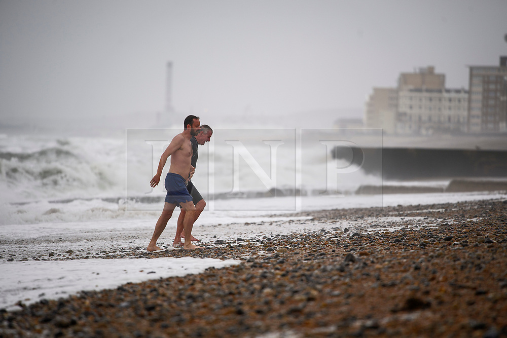 © Licensed to London News Pictures. 18/09/2018. Brighton, UK. Two men brave a dip in rough sea waters during wet and windy conditions on the sea front at Brighton. The recent warm spell is set to change for many over the next few days in the south. Photo credit: Ben Cawthra/LNP