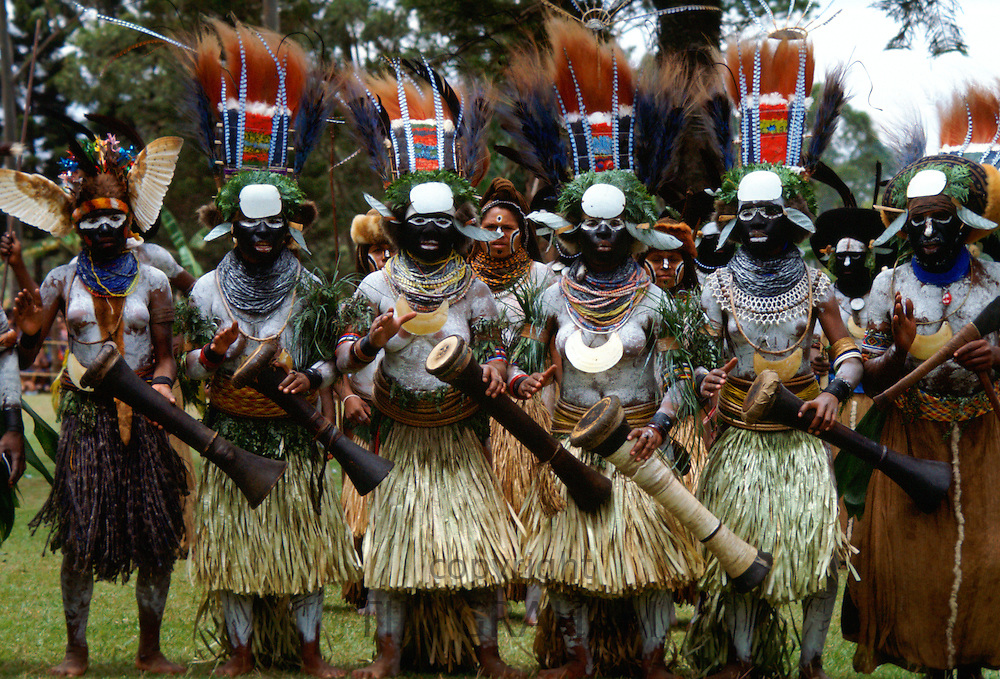 Tribeswomen musicians in feathered headdresses grass skirts and face paints playing drums during  a gathering of tribes at Mount Hagen in Papua New Guinea