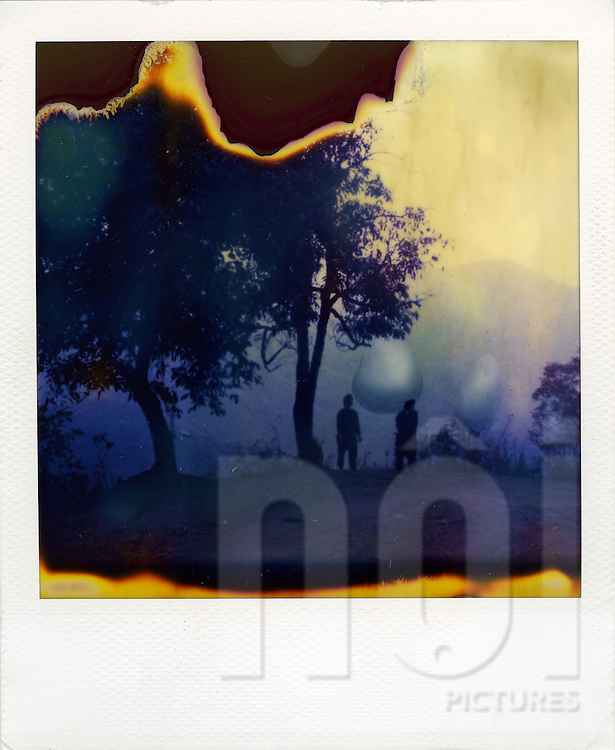 Mystic picture of a real outdated polaroid. Two strange silhouette stand close trees. Asia, Vietnam