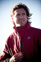 Young man wearing red/maroon sports jacket with blue sky backgroud