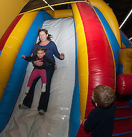 """Rowan Sottak and Jackie Viar go for a slide during the first annual """"Jump a Thon"""" on Sunday at Jump 'n Joy to benefit the WLNH Children's Auction.  (Karen Bobotas/for the Laconia Daily Sun)"""