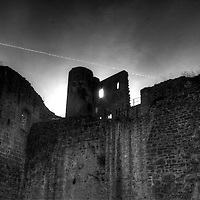 The setting sun glows behind the wall in the view from the Hardenburg castle (circa 1214) courtyard looking west up towards the forecourt area - B&W version