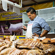 Man working in a butcher shop at a market in Cholula, Mexico
