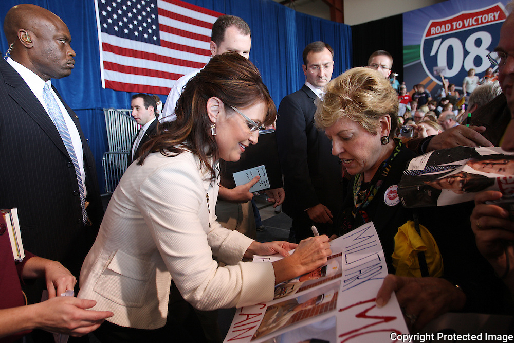 U.S. Republican vice presidential nominee Governor Sarah Palin autographs a sign for a supporter after a campaign rally in Cedar Rapids, Iowa, September 18, 2008.