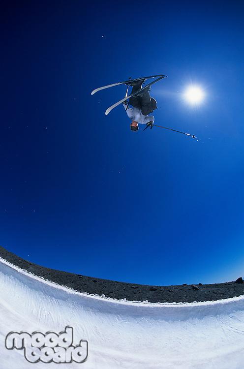 Skier performing flip on mountain