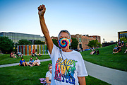 21 JULY 2020 - DES MOINES, IOWA: JANE WEATHERS holds up her fist to salute late Representative John Lewis (D-GA) during a memorial and vigil for the Congressman. About 300 people attended a vigil for the late Representative in Poppajohn Sculpture Park in Des Moines Tuesday night. Rep. Lewis died from pancreatic cancer on July 17, 2020.            PHOTO BY JACK KURTZ