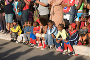 Children at the pavement, watching Carnival pageant. Mindelo. Cabo Verde. Africa.