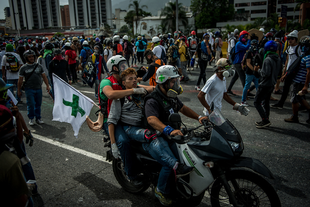 "CARACAS, VENEZUELA - MAY 22, 2017:  Medical students volunteer on the front line of clashes as ""Green Helmets"" - first responders that evacuate and give first aid to injured protesters.  Many young medical students are angry about the poor state of the public healthcare system.  Over 85 percent of medicines are either impossible, or very difficult to find in Venezuela.  Public hospitals face shortages of even the most basic supplies, like gauze, latex gloves, syringes - even running water. Many say they see volunteering with the Green Helmets as using their talents to supporting the protest movement taking over the streets of Caracas. PHOTO: Meridith Kohut"