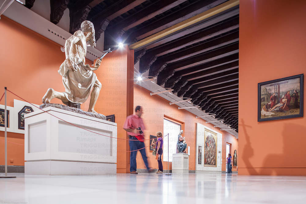 Visitors in the Room II, Renaisance Art, Museum of Fine Arts, Seville, Spain. On the left, Saint Jerome sculpture by Pietro Torrigiani.