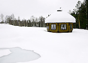 Lapland, Scandinavia, a snow covered wooden sauna shed, in a landscape of snow