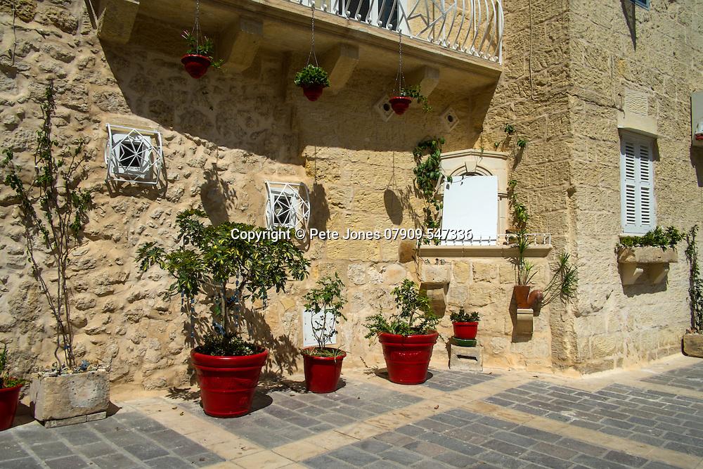 Red flower pots outside restaurant,<br />Mdina,<br />Malta, Europe.<br />Summer 2016.
