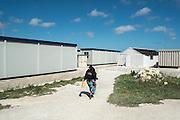 Malta, Hal Far. Open Center. Una donna va a prendere l'acqua alla fontana, nei container adibiti ad abitazioni non sono presenti ne acqua corrente ne servizi igenici