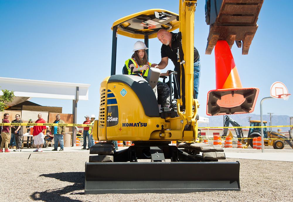 mkb042117c/metro/Marla Brose --  Calypso Tucker, an 8th grader from Albuquerque Sign Language Academy, picks up and stacks cones as she operates a mini-excavator with instruction from Robert Carrillo from Komatsu SW, during the Heavy Equipment Rodeo and Job Fair at ACE Leadership High School in Albuquerque, N.M., Friday, April 21, 2017. The second annual rodeo, which provided students from various programs the opportunity to have hands-on experience, was sponsored by AGC New Mexico and Associated Contractors of New Mexico. (Marla Brose/Albuquerque Journal)