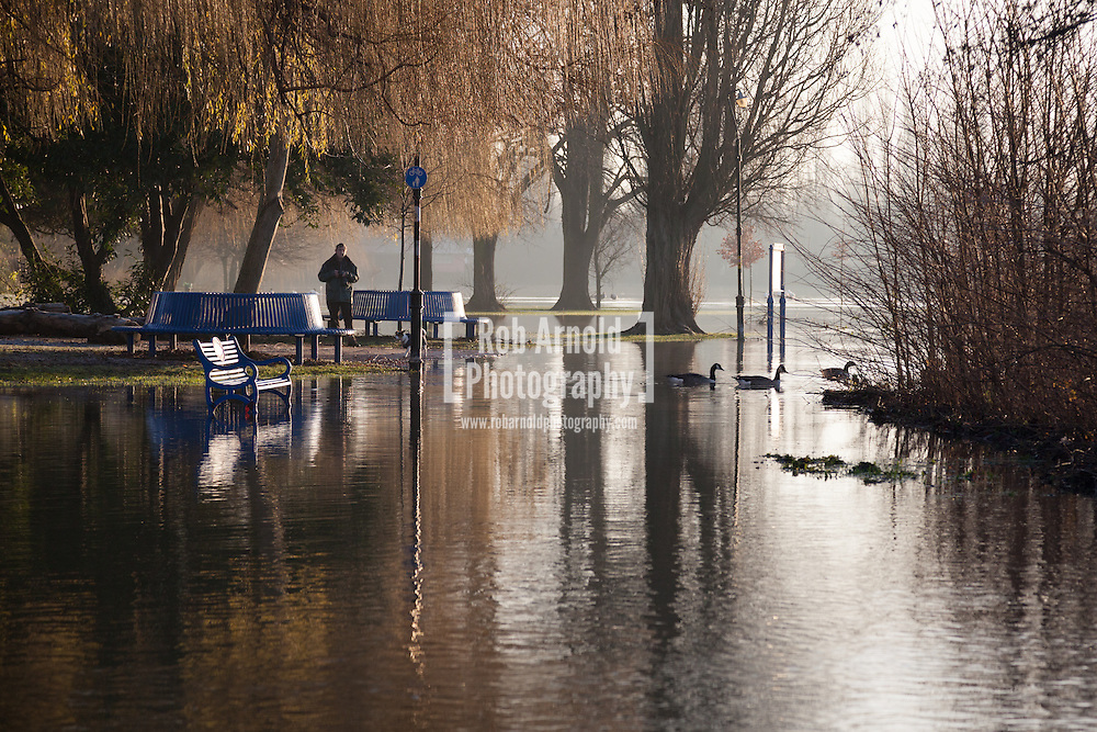 12/01/2014. Reading, Berkshire, UK. A man observes the flood water at Christchurch Meadows along the Thames Path in Reading, Berkshire. The River Thames has broken its banks causing extensive flooding. Photo by Rob Arnold