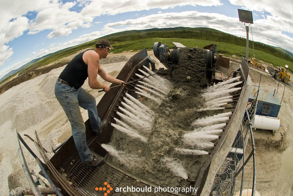 A gold mine worker feeds the gravel through the sluice.<br /> <br /> NOT IN YOUR BUDGET? Contact Cathie for a price specific to your project.