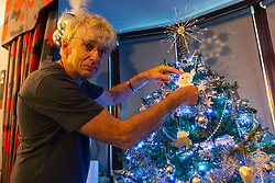 Geoff Stonebanks, 66, decorates the silver and gold themed Christmas tree in his home in Seaford, East Sussex, where he uses over 3,800 decorations on more than a dozen trees, creating a magical effect that truly celebrates the festive season. Seaford, East Sussex, December 03 2018.