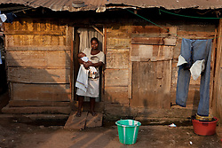 Melanie and her baby son outsides their shack in a slum area in Yaounde. Last year her first son died, he was a small and sick for a while, but she is not sure what exactly killed him. She is worried the council will knock down their area and they will be homeless. Yaounde, Cameroon.