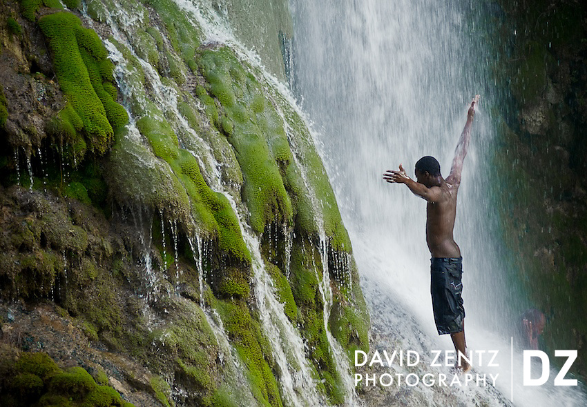A young man worships beneath the cascading falls at Saut D'eau in central Haiti during the annual voodoo festival held there, on July 15, 2008.