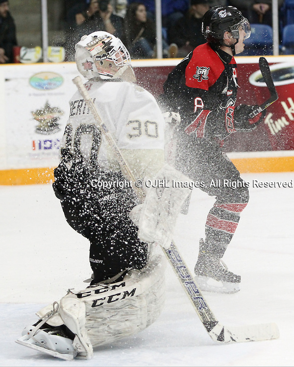 TRENTON, ON  - APR 15,  2017: Ontario Junior Hockey League, Championship Series. Georgetown Raiders vs the Trenton Golden Hawks in Game 2 of the Buckland Cup Final. Elliot Gerth #30 of the Trenton Golden Hawks gets a snow shower from Ryan Takamatsu #8 of the Georgetown Raiders during the first period.<br /> (Photo by Tim Bates / OJHL Images)