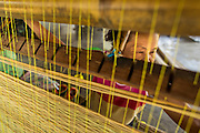 25 APRIL 2014 -  MAE CHAN, CHIANG RAI, THAILAND: A woman weaves papyrus reed matts by hand at her family home in Mae Chan, Chiang Rai province, Thailand. Families in Chiang Rai province still make woven reed matts by hand. The matts are used around the house as an impromptu table, and farmers as something to spread out on the ground during lunch, like a picnic blanket. They cost anywhere from 15Baht (.50¢ US) to 150Baht ($5.00 US) depending on size.    PHOTO BY JACK KURTZ