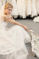Beautiful young woman confused with footwear selection in bridal store