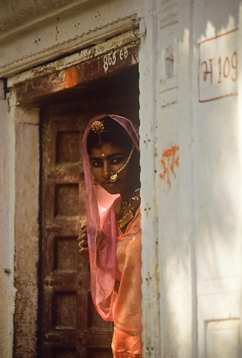 beautiful Rajasthani woman in traditional dress at front door of her home in Jaisalmer India