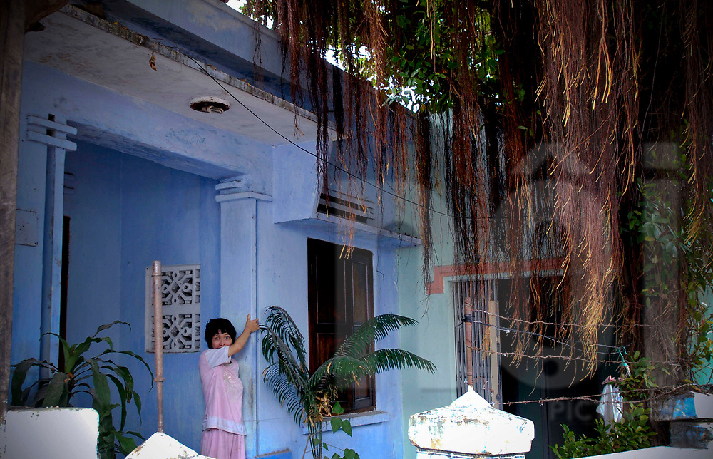 A mentally ill woman stands in front of her entryway, Tam Hai, Vietnam, Southeast Asia