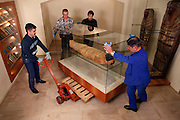 """GEORGES LABIT MUSEUM, TOULOUSE, FRANCE - MARCH 03 - EXCLUSIVE : A general view of the Egyptian mummy encased in a sarcophagus moved by warehousemen on March 3, 2009 in the Georges Labit Museum, Toulouse, France. The Egyptian mummy arrived in Toulouse in 1849, encased in a sarcophagus labelled """"In-Imen"""" from the 7th or 8th century BC. It is preserved at the Labit Museum since 1949. The mummy has been the subject of a very rare tissue sampling operation to determine its datation.  (Photo by Manuel Cohen)"""