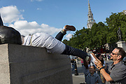 Helped by her partner, a woman tourist attempts to climb on to one of the four lions at the base of Nelson's Column in Trafalgar Square, on 10th August 2017, in London, England.