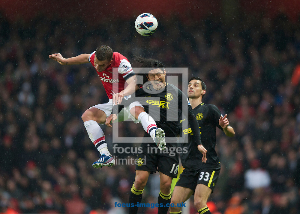 Picture by Alan Stanford/Focus Images Ltd +44 7915 056117.14/05/2013.Lukas Podolski of Arsenal and Roger Espioza of Wigan Athletic challenge for the ball during the Barclays Premier League match at the Emirates Stadium, London.