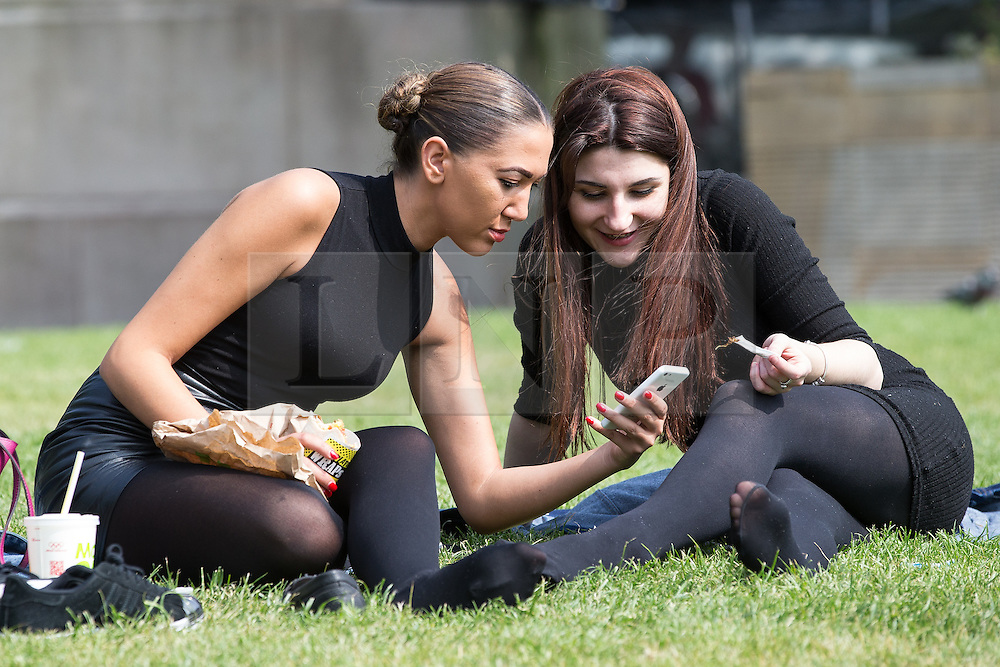 © Licensed to London News Pictures . 09/06/2016 . Manchester , UK . Two women sitting on the grass in Manchester's Piccadilly Gardens , in the sunshine . Hot weather returns to the region following heavy storms and flooding . Photo credit : Joel Goodman/LNP