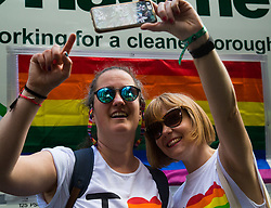 London, July 8th 2017. Thousands of LGBT+ revellers take part in the annual Pride in London parade under the banner #LoveHappensHere. PICTURED: Two women take a selfie.