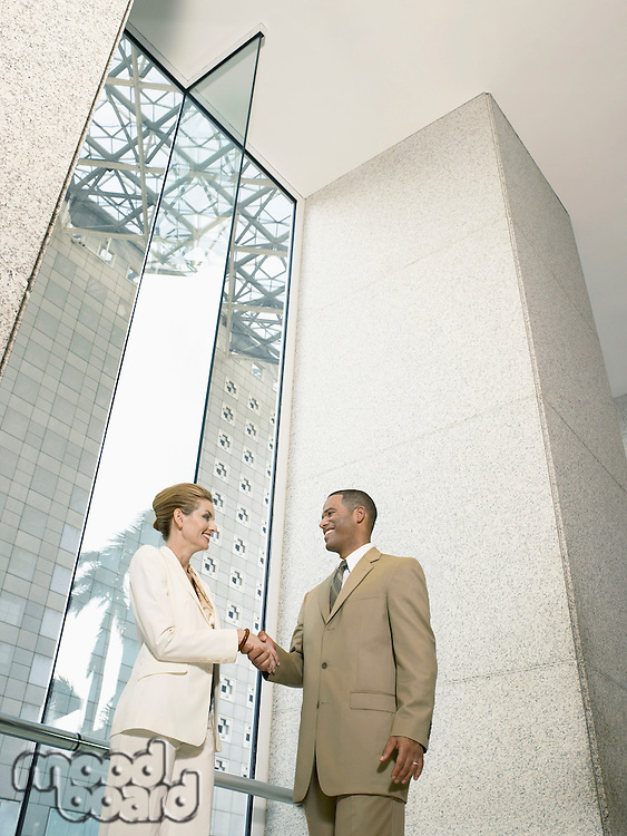 Businesspeople shaking hands in office building (low angle view)