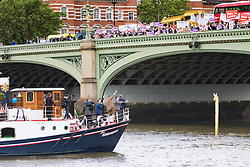 London Bridge, London, June 15th 2016. A flotilla of fishing boats led by UKIP's Nigel Farage heads through Tower Bridge in protest against the EU's Common Fisheries Policy and in support of Britain leaving the EU. PICTURED: Farage's boat passes under Westminster Bridge as above supporters cheer and counter protesters jeer, while one of his people makes an obscene gesture with both hands.