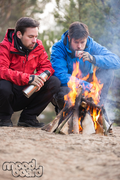 Male backpackers having coffee at campfire in forest
