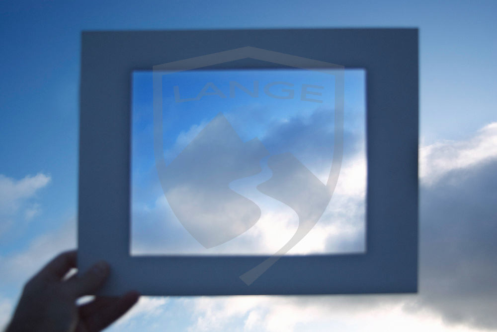a hand holds up  a frame to picture the morning clouds in the san francisco bay area, california, usa
