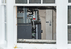 © Licensed to London News Pictures. 28/10/2015. Thornbury, South Gloucestershire, UK. Picture of the back of the ATM.  A suspected raid on Barclays Bank in Thornbury High Street occurred at 3.30am.  An ATM in a foyer corridor with 24 hrs access was targeted, and an explosion damaged the interior.  A gas bottle can be seen in the foyer corridor and a large hammer and crowbar were left at the scene. Photo credit : Simon Chapman/LNP