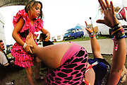 A woman prepares to lift a child with her legs,  Boomtown, Matterley Estate, Alresford Road, Winchester, Hampshire, UK, August, 2010