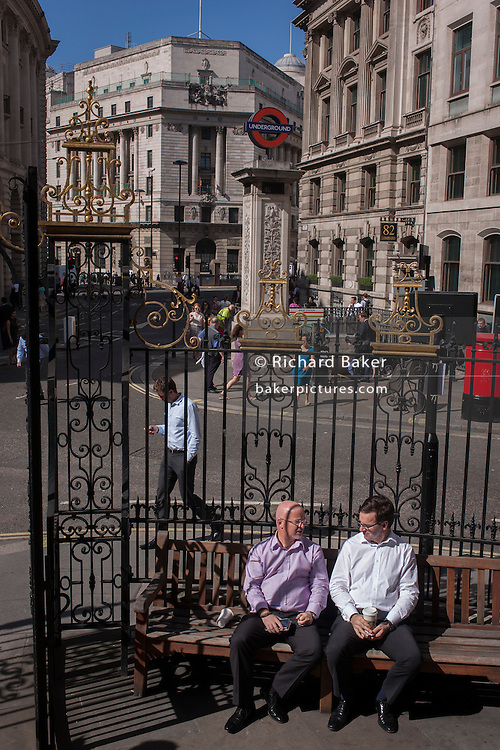 Lunchtime rest from the office for two businessmen, seated on a bench at the corner of King William and Lombard Streets.