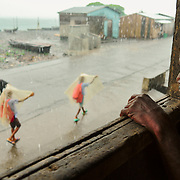 Children returning from school on a rainy day, at the fishing village of Santa Catarina.