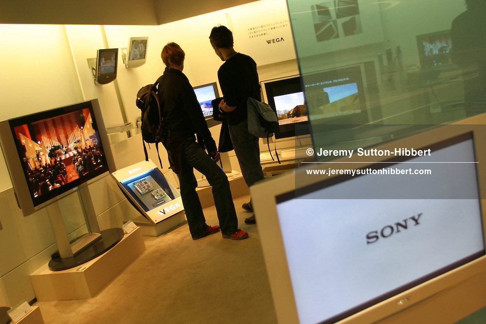 In the Sony Building showroom a customers view the latest widescreen televison products by Sony. The Sony building houses 6 floors showcasing their products and designs, in the up-market Ginza area of the city.