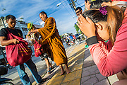 25 OCTOBER 2012 - PATTANI, PATTANI, THAILAND:  A Buddhist woman prays as monks pass her on their alms rounds in Pattani, Thailand. More than 5,000 people have been killed and over 9,000 hurt in more than 11,000 incidents, or about 3.5 a day, in Thailand's three southernmost provinces and four districts of Songkhla since the insurgent violence erupted in January 2004, according to Deep South Watch, an independent research organization that monitors violence in Thailand's deep south region that borders Malaysia.    PHOTO BY JACK KURTZ