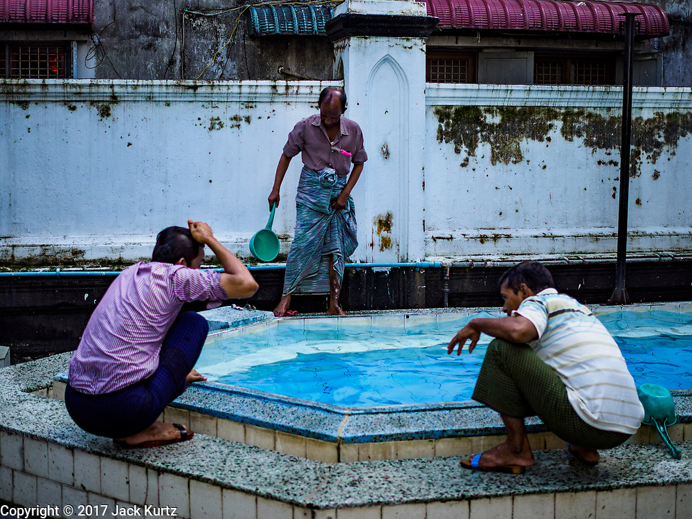"""24 NOVEMBER 2017 - YANGON, MYANMAR: Muslim men perform ablutions before Friday prayers at Mogul Shiah Mosque in Yangon. Many Muslims in overwhelmingly Buddhist Myanmar feel their religion is threatened by a series of laws that target non-Buddhists. Under the so called """"Race and Religion Protection Laws,"""" people aren't allowed to convert from Buddhism to another religion without permission from authorities, Buddhist women aren't allowed to marry non-Buddhist men without permission from the community and polygamy is outlawed. Pope Francis is to arrive in Myanmar next week and is expected to address the persecution of the Rohingya, a Muslim ethnic minority in western Myanmar. Some Muslims and Christians are concerned that if the Pope's comments take too strong of pro-Rohingya stance, he could exacerbate religious tensions in the country.  PHOTO BY JACK KURTZ"""
