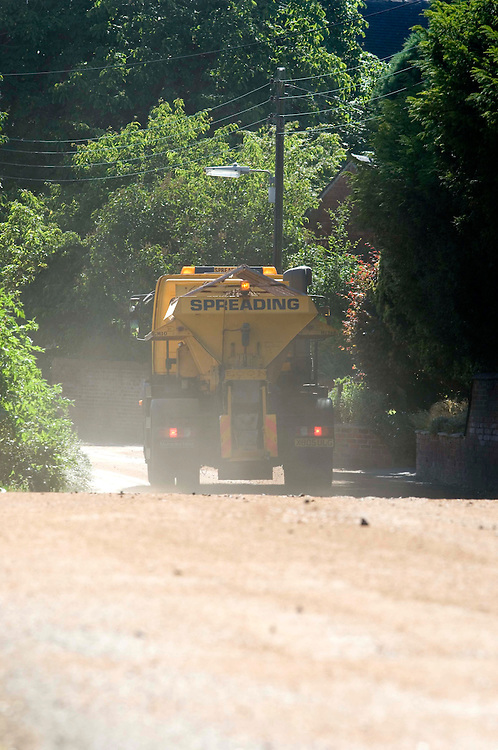 Road gritters spread sand on the Tarmac roads that are melting, in the heatwave, Marchington, Staffordshire, United Kingdon