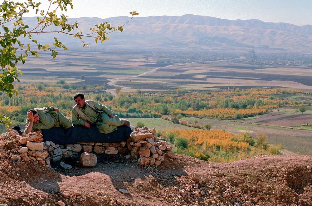Two Kurdish Peshmerga fighters rest and warm themselves in the early morning sun at their front line position over looking the town of Halabja.<br /> Halabja, Iraqi Kurdistan. 20/11/2002