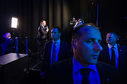 Diplomatic Protection Squad assigned body guards keep vigil as John Key is interviewed for the TV networks at the Viaduct Event Centre.  <br /> 2014 New Zealand General Election night photography commissioned by The NZ Listener magazine.