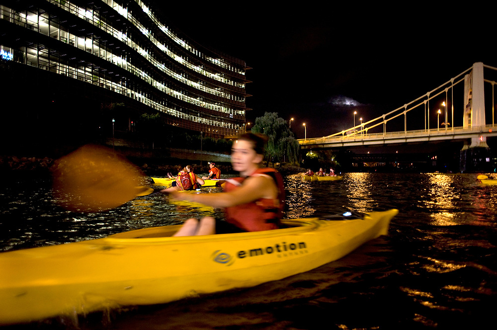 A kayaker paddles past the Alcoa Building along the Allegheny River in Pittsburgh while participating in Venture Outdoors' Fireworks Paddle.
