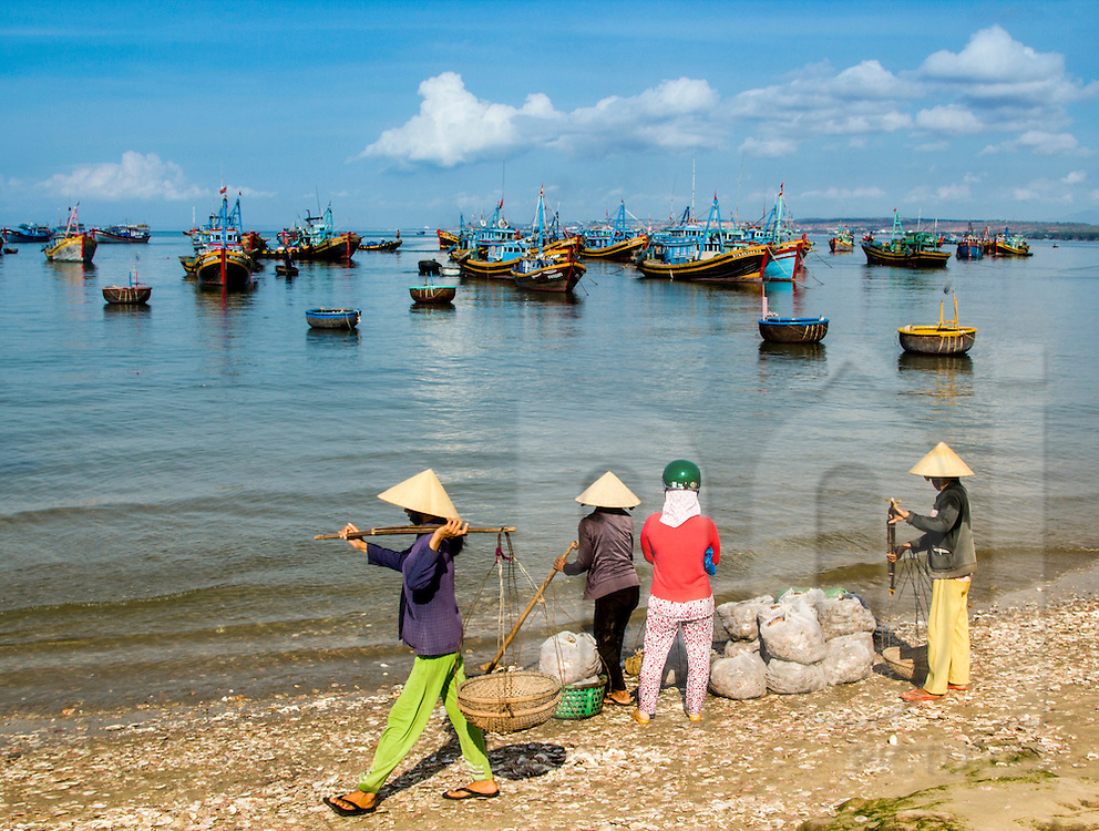 Vietnamese women carry sea products on a beach in Mui Ne, Vietnam, Southeast Asia