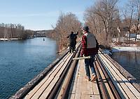 Tyler Emond with fishing rod in hand heads across the bridge at the Winnipesaukee River between Lake Opechee and Lake Winnisquam on opening day for landlocked fishing season.  (Karen Bobotas/for the Laconia Daily Sun)